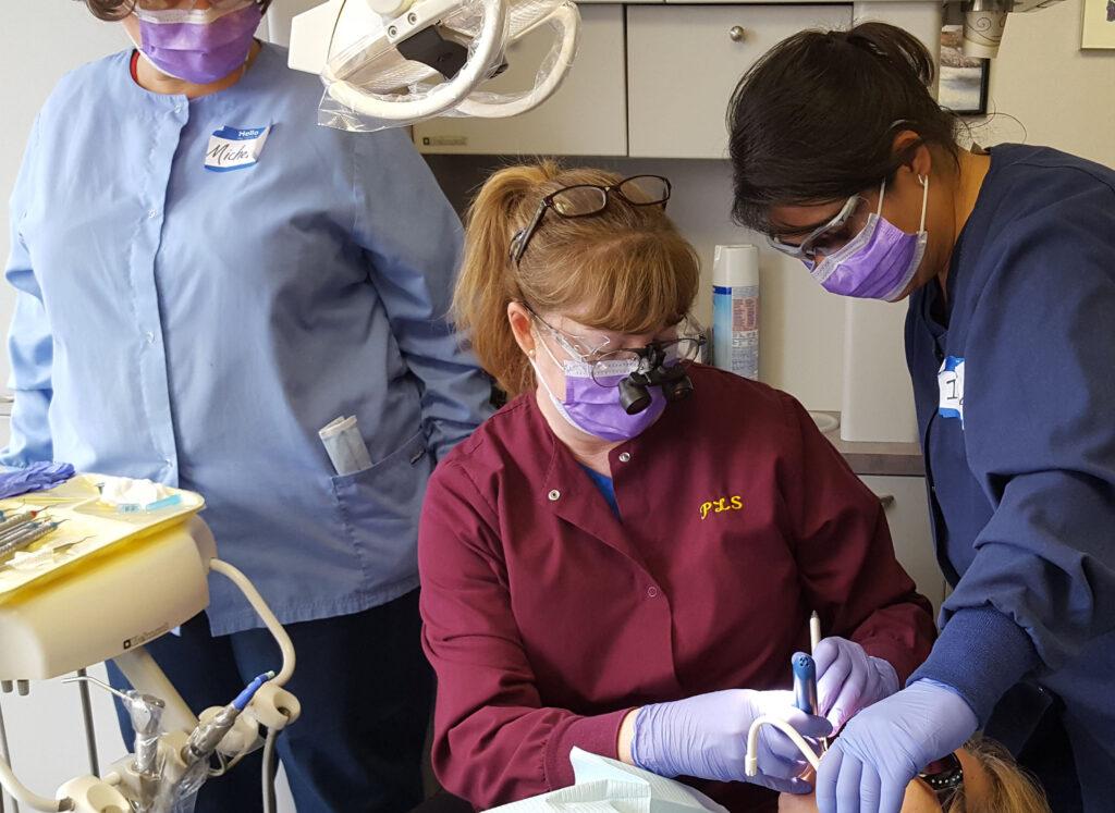 three dental hygienists receiving instruction